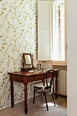 Antique writing desk with mirror and Thonet chair against wall with floral wallpaper below window with white interior shutters
