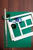Green construction paper, white picture frame, photo mount, metal ruler and velcro tape on wooden surface