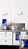 Two hand-crafted pendant lamps made from enamel bowls above kitchen sink with retro-style draining rack