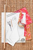 Fabric swatch, white paper, scissors, ruler and wooden rod