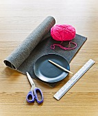 Roll of grey felt, ball of pink wool, plate, scissors and ruler