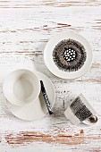 White crockery decorated with black ceramic marker on white, distressed wooden surface