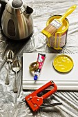 Pot of yellow paint, stapler, white skirting board and dessert spoons