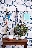 White wardrobe on wall with blue and white floral motif; in front of it dried hydrangea flowers in a balloon vase standing on a vintage table