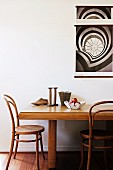 Solid wood dining table with vintage chairs; a black and white poster on the wall