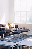 Original stool with seat cushion and sofa with large decorative cushions in the sun-drenched corner of the room