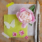 Peony, sheets of paper, paper butterfly, pink flowers and twigs