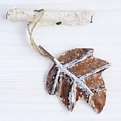 Brown leaf hanging from birch twig as pendant