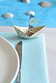 Paper boat with name on flag as place card next to place setting