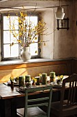 Spring atmosphere; dining table decorated with candles and flowers below window with china jug of forsythia branches on windowsill