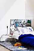 Teenager's bed with grey magnetic pinboard on wall, pillow painted with faces and blue bedspread next to table lamp on small metal table
