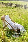 Liegestuhl mit Strohhut, Kissen und Buch auf einer Sommerwiese