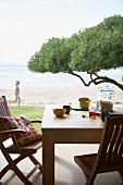 Two wooden chairs and table set for breakfast on terrace with view of tree canopy and ocean beach