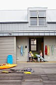 Paddles and kayak on wooden terrace in front of beach house with industrial-style sheet metal roof; swimming gear and children playing in open-plan corridor