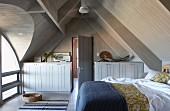 Bedroom with double bed and sideboards below pitched roof with light falling though arched dormer window