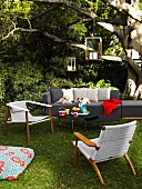 Seating area in garden with sofa, tables, chairs, lanterns and floor cushion