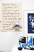 Enlarged, hand-written letter as wall decoration behind blue pendant lamp