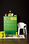 Green chest of drawers on black wall; next to it a white plastic chair and a children's stool