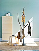 Coat rack hand crafted from tree trunk with shoe cabinet in background and stool on sisal rug