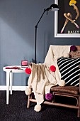 Pale, knitted blanket decorated with colourful wool pompoms on wicker chair