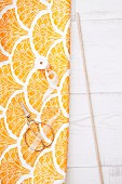 Length of fabric with yellow and orange pattern, scissors and wooden rod