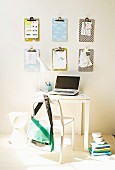 Hand-crafted clipboards on wall above small, white desk with laptop and white chair