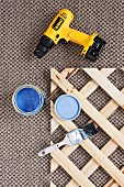 Yellow cordless drill-driver, pot of blue paint, paintbrush and cut-down section of wooden trellis