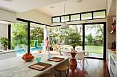 Theke mit Tischset in modernem, offenen Wohnraum und Blick auf Pool im Garten