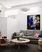Lounge area with designer furniture and brightly coloured artwork on wall next to white partition