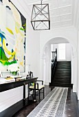 High-ceilinged entrance area with stucco ceiling and staircase leading through arched doorway; large modern painting on wall above narrow, black, antique console table