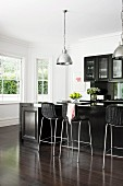 Elegant, black fitted kitchen with counter and bar stools on fine, dark parquet floor; white bay window and chrome pendant lamps