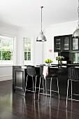 Elegante schwarze Einbauküche mit Theke und Barhockern auf edlem dunklem Parkett vor weißen Erkerfenstern, darüber verchromte Pendelleuchten.