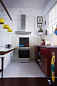 Kitchen with yellow pendant lamps above counter and free-standing cooker below extractor hood