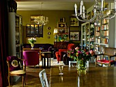 View across dining table below chandelier into atmospheric living area with armchairs in various colours