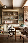 Shaker-style dresser and wooden armchairs in kitchen-dining room of old, renovated dairy in South Africa