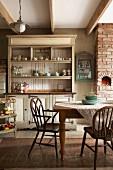 Geschirrschrank und Armlehnstühle im Shakerstil in der Wohnküche einer alten, umgebauten Molkerei in Südafrika