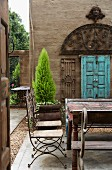 French wire chairs, monastery table and artistic, delicate, Indian iron window in courtyard with floor made from large concrete slabs and gravel strips