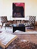 Two retro armchairs with geometric upholstery in front of modern painting of horse; hand-crafted patchwork leather easy chair and rugs in foreground