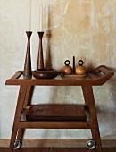 Kunsthandwerkliche Gefässe und Kerzenhalter aus Holz und ein Stapel mit Sets aus Lederpatchwork auf einem Teewagen vor antik marmorierter Wand