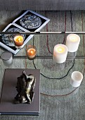 Sculpture and candles on glass table with view of graphic pattern on rug below and open book