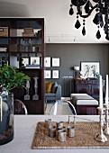 Esstisch mit Silbergerät auf geflochtenem Set; Wohnraum mit Kunstwerken und eleganten Möbeln vor dunkel getönter Wand