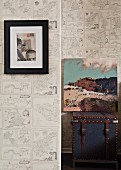 Framed artwork and unframed painting on trunk against wallpaper with pattern of maps