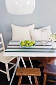 Mit unterschiedlichen Streifen gestaltete Tischplatte auf Holzböcken, rundum Sitzgelegenheiten und weiße Kissen vor pastellblauer Wand