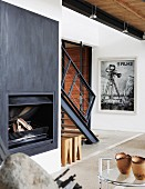 Open fireplace with metal surround in living room; staircase in background