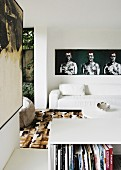 Living room with white leather sofa and modern artworks on walls
