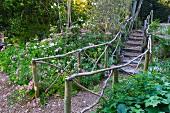 Gravel path with wooden railing in flowering garden