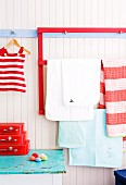 Red-painted wooden frame with crossbar for hanging various textiles in child's bedroom next to child's red and white striped dress hanging from blue row of clothes pegs