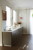 Kitchen counter with dark base units below window and walls painted pale grey