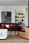 Hocker mit Tierfellbezug und Sitzmöbel aus Leder in klassisch traditionellem Wohnzimmer mit Einbauregal