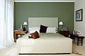Simple bed with headboard against green-painted wall in classic bedroom